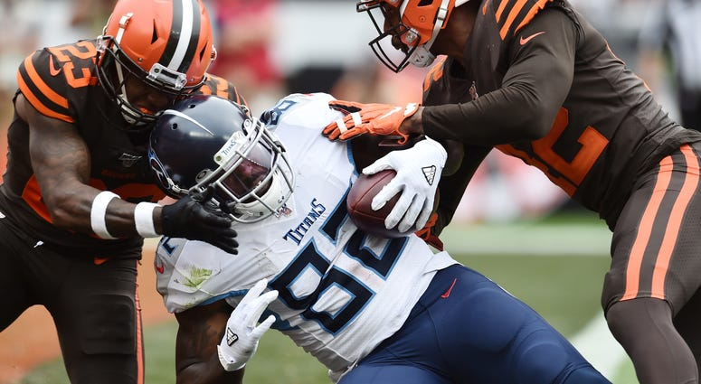 Tennessee Titans tight end Delanie Walker (82) scores a touchdown as Cleveland Browns strong safety Damarious Randall (23) and strong safety Morgan Burnett (42) defend
