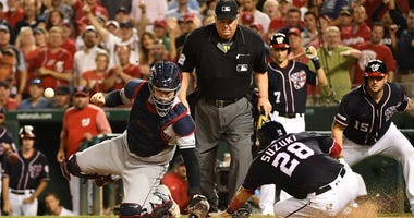 Washington Nationals catcher Kurt Suzuki (28) scores a run as Cleveland Indians catcher Roberto Perez (55) is unable to control the ball during the sixth inning at Nationals Park.