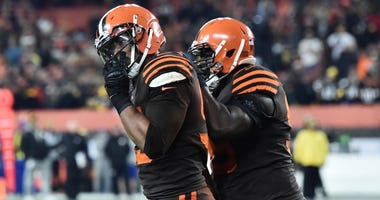 Cleveland Browns defensive tackle Devaroe Lawrence (99) leads defensive end Myles Garrett (95) off the field after a fight during the second half against the Pittsburgh Steelers at FirstEnergy Stadium.