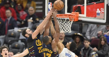 Nov 27, 2019; Cleveland, OH, USA; Cleveland Cavaliers forward Larry Nance Jr. (22) and center Tristan Thompson (13) reach for a rebound beside Orlando Magic center Khem Birch (24) in the fourth quarter at Rocket Mortgage FieldHouse. Mandatory Credit: Davi