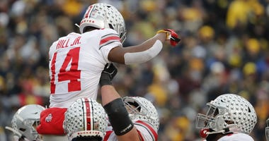 Ohio State Buckeyes wide receiver K.J. Hill (14) is congratulated by teammates after he scores a touchdown in the second half against the Michigan Wolverines at Michigan Stadium.