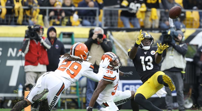 Dec 1, 2019; Pittsburgh, PA, USA; Pittsburgh Steelers wide receiver James Washington (13) catches a touchdown pass against Cleveland Browns defensive back T.J. Carrie (38) and defensive back Sheldrick Redwine (29) during the second quarter at Heinz Field.