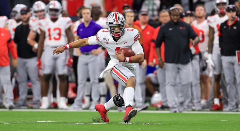 Dec 7, 2019; Indianapolis, IN, USA; Ohio State Buckeyes quarterback Justin Fields (1) carries the ball against the Wisconsin Badgers during the first half in the 2019 Big Ten Championship Game at Lucas Oil Stadium. Mandatory Credit: Aaron Doster-USA TODAY