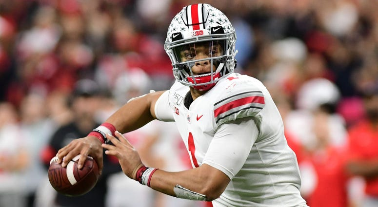 Ohio State quarterback Justin Fields (1) rolls out of the pocket to throw for a touchdown in the second half against the Wisconsin Badgers in the 2019 Big Ten Championship Game at Lucas Oil Stadium.