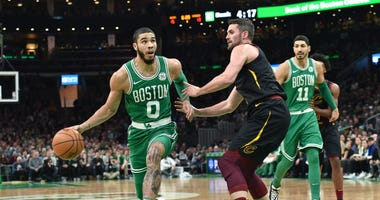 Boston Celtics forward Jayson Tatum (0) drives to the basket while Cleveland Cavaliers forward Kevin Love (0) defends