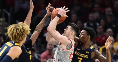 Dec 29, 2019; Cleveland, Ohio, USA; Ohio State Buckeyes forward Kyle Young (25) shoots between West Virginia Mountaineers forward Gabe Osabuohien (3) and guard Jermaine Haley (10) during the first half at Rocket Mortgage FieldHouse.