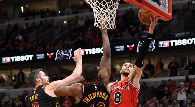 Chicago Bulls guard Zach LaVine (8) shoots the ball as Cleveland Cavaliers center Tristan Thompson (13) and forward Kevin Love (0) defend during the second half at United Center