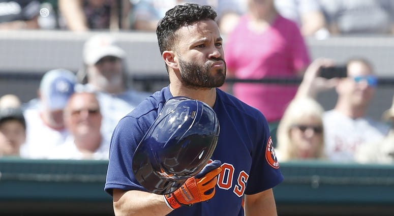 Houston Astros second baseman Jose Altuve (27) recovers his helmet after it fell off on a swing during the first inning against the Detroit Tigers at Publix Field at Joker Marchant Stadium.