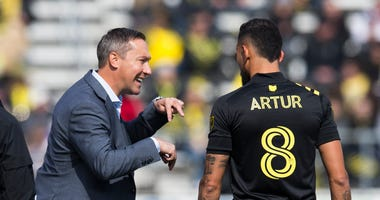 Columbus Crew SC head coach Caleb Porter talks with midfielder Artur (8) as an injured New York City FC player is treated in the first half at MAPFRE Stadium.
