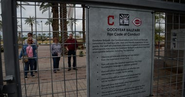Fans stand outside of Goodyear Ballpark after the spring training game between the San Diego Padres and Cleveland Indians was canceled.
