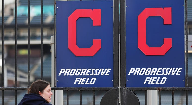 Mar 26, 2020; Akron, OH, USA; Cleveland Indians fan Melissa Dallachiesa of Cleveland leans on the left field gate outside Progressive Field in Cleveland, Ohio. The Indians were scheduled to play the Detroit Tigers, but the season has been delayed due to t