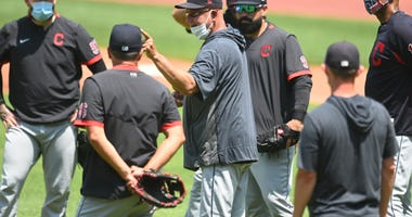 Cleveland Indians manager Terry Francona (middle, mask on chin)