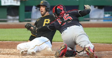 Pittsburgh Pirates catcher Jacob Stallings (58) slides across home plate to score a run ahead of the tag attempt of Cleveland Indians catcher Roberto Perez (55) during the fifth inning at PNC Park.