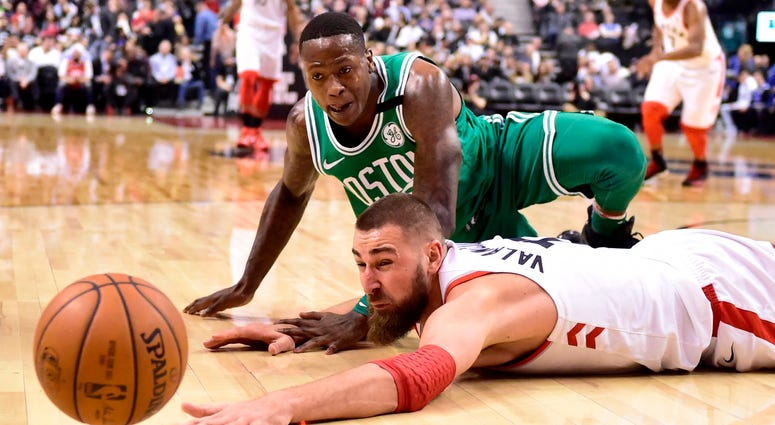 Toronto Raptors center Jonas Valanciunas and Boston Celtics guard Terry Rozier watch the ball get away during the second half of an NBA basketball game Wednesday, April 4, 2018, in Toronto. (Frank Gunn/The Canadian Press via AP)