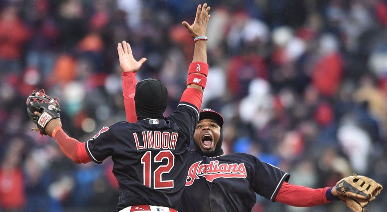 Cleveland Indians shortstop Francisco Lindor (12) and center fielder Rajai Davis (26) celebrate after defeating the Kansas City Royals at Progressive Field.