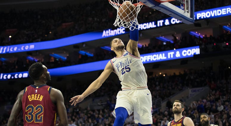 Philadelphia 76ers guard Ben Simmons (25) dunks past Cleveland Cavaliers forward Jeff Green (32) and center Kevin Love (0) during the second quarter at Wells Fargo Center