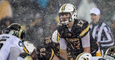 Wyoming Cowboys quarterback Josh Allen (17) calls a play against the Colorado State Rams during the fourth quarter at War Memorial Stadium.