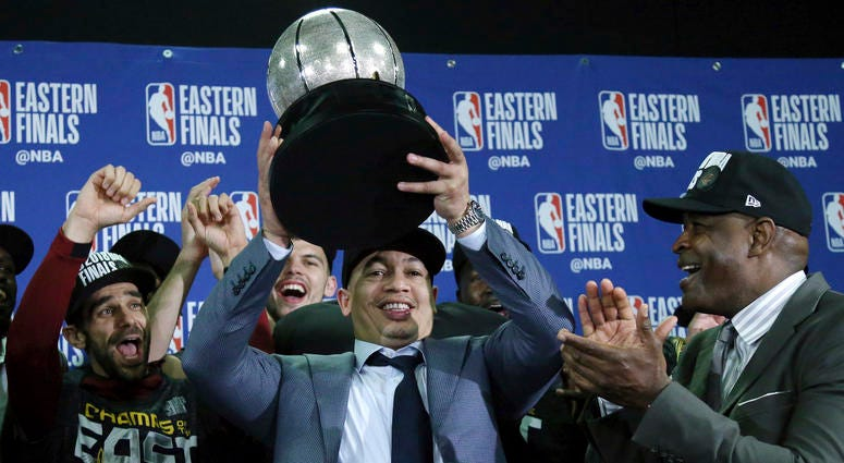 Cleveland Cavaliers head coach Tyronn Lue hoists the trophy after beating the Boston Celtics 87-79 in Game 7 of the NBA basketball Eastern Conference finals, Sunday, May 27, 2018, in Boston.