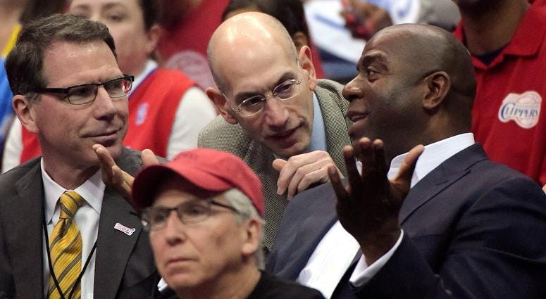 n this May 11, 2014, file photo, NBA Commissioner Adam Silver, center, talks with Magic Johnson, right, as Kiki Vandeweghe looks on