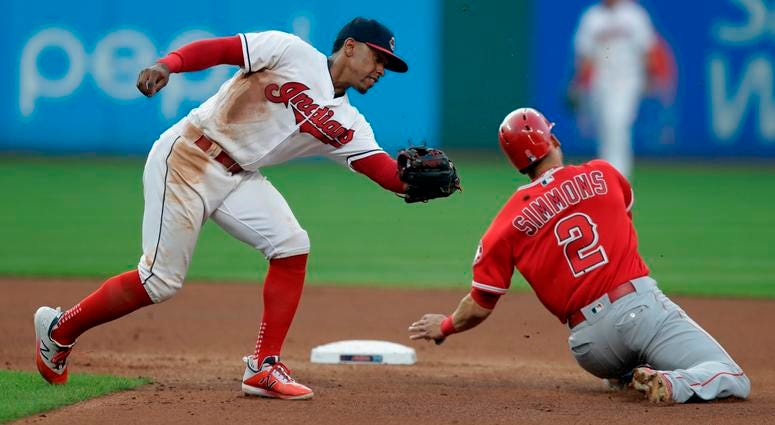 Cleveland Indians' Francisco Lindor, left, cannot make the tag as Los Angeles Angels' Andrelton Simmons slides safely into second base in the fourth inning of a baseball game, Saturday, Aug. 4, 2018, in Cleveland.
