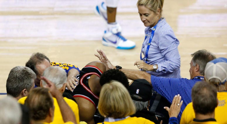 OAKLAND, CALIFORNIA - JUNE 05: Kyle Lowry #7 of the Toronto Raptors is pushed by Warriors minority investor Mark Stevens (blue shirt) after falling into the seats after a play against the Golden State Warriors in the second half during Game Three of the 2