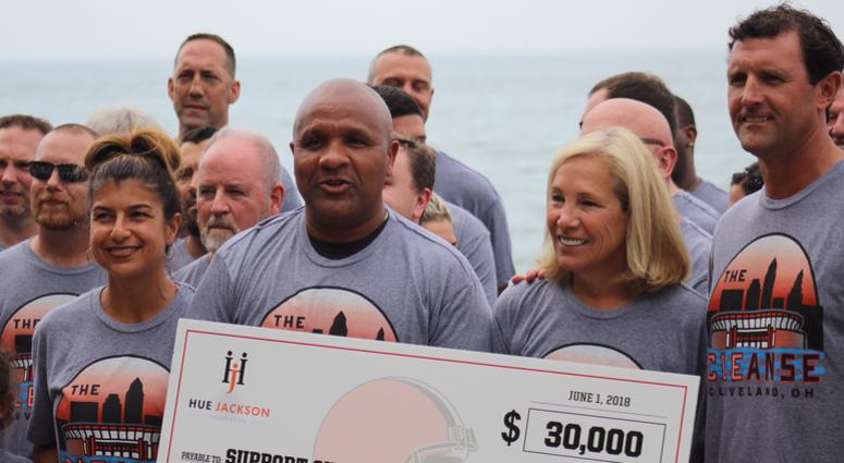 Browns owner Dee Haslam poses with coach Hue Jackson and a $30,000 donation for his foundation prior to his swim in Lake Erie on June 1, 2018.