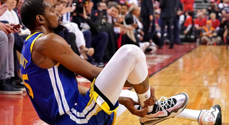 Golden State Warriors forward Kevin Durant (35) sits on the court after an apparent injury during the second quarter in game five against the Toronto Raptors of the 2019 NBA Finals at Scotiabank Arena.