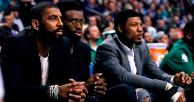 Boston Celtics guard Kyrie Irving, left, sit with teammates Jaylen Brown, center, and Marcus Smart during the first quarter of the team's NBA basketball game against the Oklahoma City Thunder, in Boston, Tuesday, March 20, 2018.