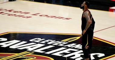 LeBron James watches during the first half of Game 4 of basketball's NBA Finals against the Golden State Warriors, in Cleveland. James has until June 29 to exercise his $35.6 million contract option for next season or decline it and become a free agent