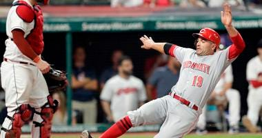 Cincinnati Reds' Joey Votto, right, scores as Cleveland Indians catcher Roberto Perez watches during the ninth inning of a baseball game Tuesday, July 10, 2018, in Cleveland. The Reds won 7-4.