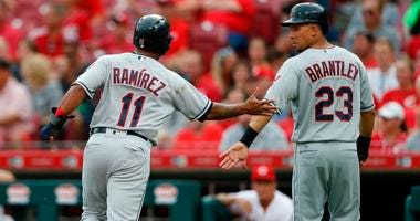 Cleveland Indians' Jose Ramirez (11) and Michael Brantley (23) celebrate after scoring on Yonder Alonso single off Cincinnati Reds starting pitcher Sal Romano during the first inning of a baseball game, Tuesday, Aug. 14, 2018, in Cincinnati.