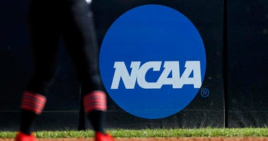 FILE - In this April 19, 2019, file photo, an athlete stands near a NCAA logo during a softball game in Beaumont, Texas. The NCAA is poised to take a significant step toward allowing college athletes to earn money without violating amateurism rules.