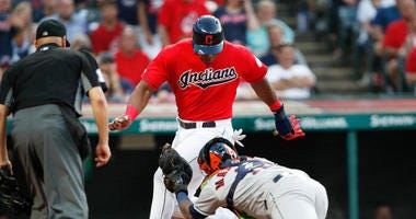 CLEVELAND, OH - AUGUST 01: Yasiel Puig #66 of the Cleveland Indians is tagged out at home plate by Martin Maldonado #12 of the Houston Astros in the fourth inning at Progressive Field on August 1, 2019 in Cleveland, Ohio. Puig and Maldonado are playing in