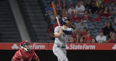 Jul 14, 2017; Anaheim, CA, USA; Tampa Bay Rays second baseman Brad Miller (13) follows through on a run-scoring single in the 10th inning as Los Angeles Angels catcher Martin Maldonado (12) watches during a MLB baseball game at Angel Stadium of Anaheim.