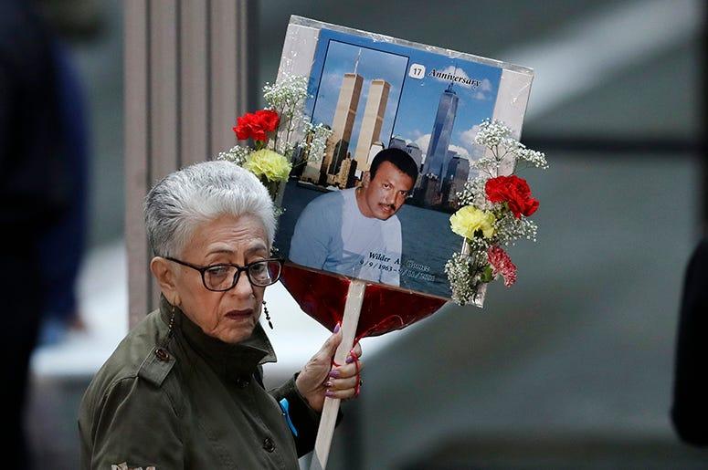 Una mujer llega a una ceremonia por el 17mo aniversario de los atentados terroristas del 11 de septiembre de 2001, con una fotografía de Wilder Gómez, un colombiano que trabajaba como camarero en el restaurante Windows on the World, en el piso 103 del Wor
