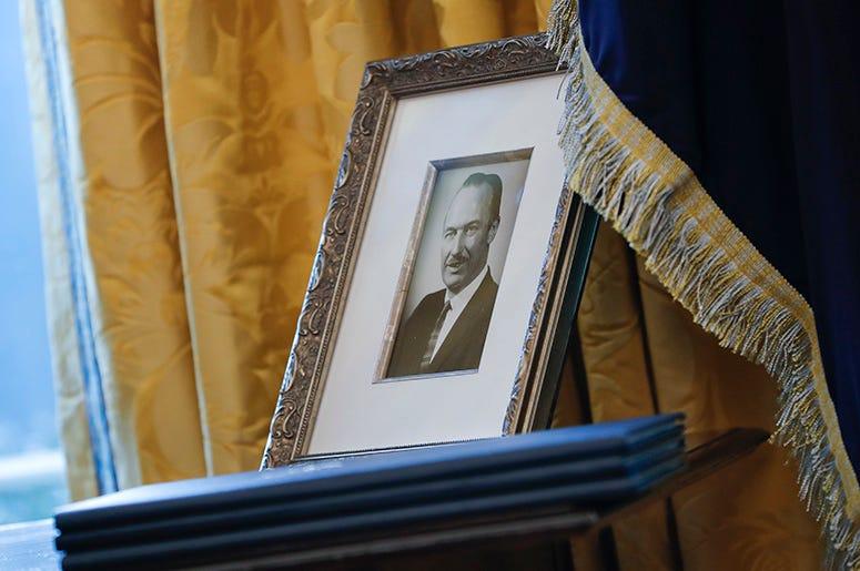 La foto de archivo del 9 de febrero de 2017 muestra un retrato de Fred Trump, padre del presidente Donald Trump y tres decretos sin firmar en la Oficina Oval de la Casa Blanca, Washington. Expertos dicen que el presidente podría tener que pagar millones e