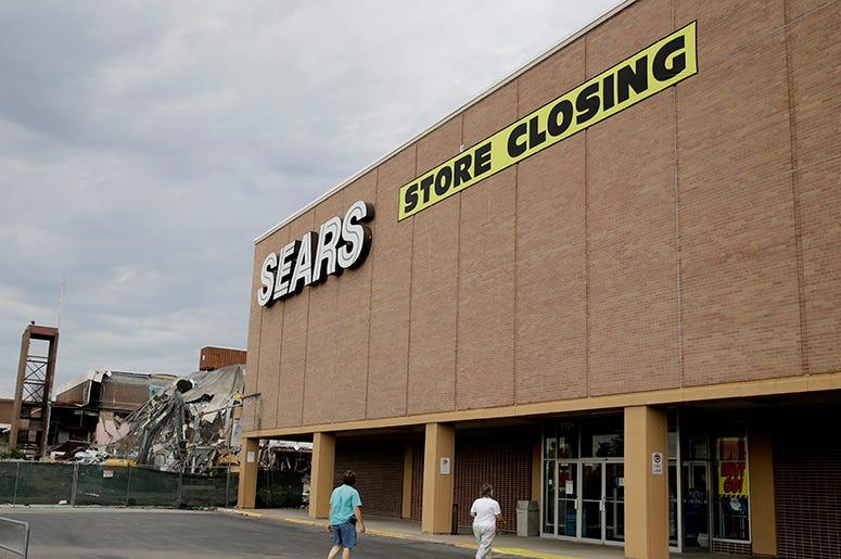 Esta foto de archivo del 8 de julio del 2017 muestra a gente caminando a una tienda de Sears que va a cerrar, ubicada al lado de un centro comercial que está siendo demolido en Overland Park, Kansas.