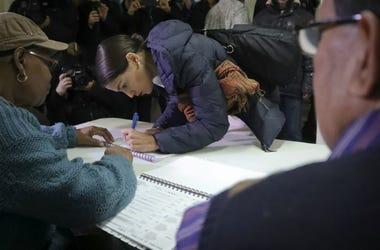 La candidata demócrata a la cámara de representantes por Nueva York Alexandria Ocasio-Cortez, al centro, firma la hoja de registros antes de votar el martes, 6 de noviembre del 2018, en la comunidad de Parkchester, en el Bronx.