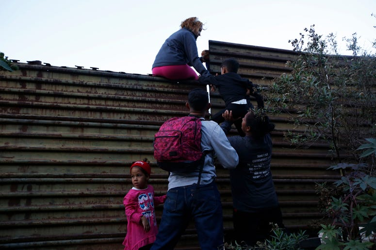 Migrantes hondureños se ayudan entre ellos para cruzar el muro fronterizo a San Diego, California, desde Tijuana, México, el sábado 15 de diciembre de 2018.
