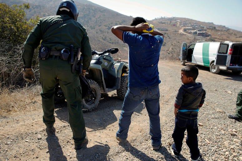 Un guatemalteco y su hijo son detenidos por agentes de la Patrulla de Fronteras tras cruzar la frontera entre México y Estados Unidos ilegalmente en San Diego el 28 de junio del 2018.