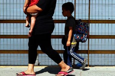 Una madre y sus dos hijos cruzan el puente del río Suchiate en momentos en que los migrantes centroamericanos cruzan la frontera entre Guatemala y México, cerca de Ciudad Hidalgo, estado de Chiapas, México, el jueves 17 de enero de 2019.