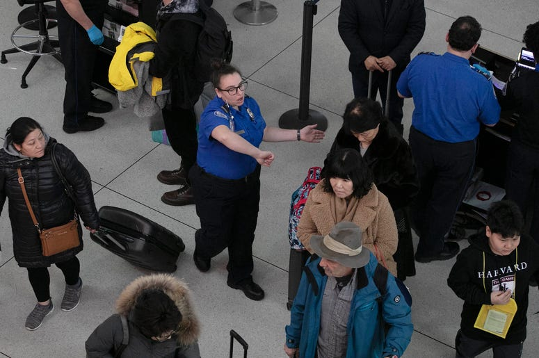 Una agente de la Administración de Seguridad en el Transporte, centro, da instrucciones a los pasajeros en un punto de revisión en el Aeropuerto Internacional John F. Kennedy, en Nueva York.