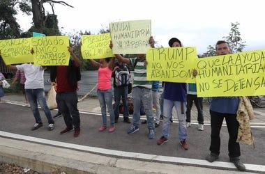 Manifestantes sostienen carteles en apoyo al autoproclamado presidente interino Juan Guaidó y a la ayuda humanitaria junto al puente internacional Las Tienditas cerca de Cúcuta, Colombia, el viernes 8 de febrero de 2019