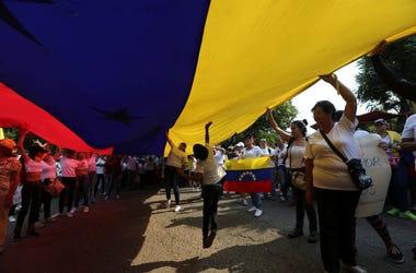 Manifestantes opositores llevan una bandera venezolana durante una protesta contra el presidente Nicolás Maduro en Urena, Venezuela, el martes 12 de febrero de 2019.