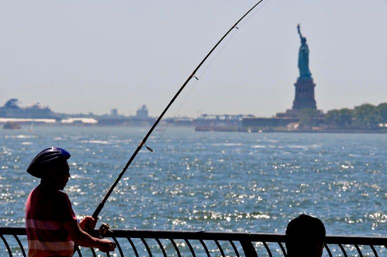 Archivo - Fotografía del 17 de junio de 2018 de un hombre pescando en el parque municipal Battery en Nueva York.
