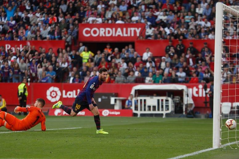 El astro argentino Lionel Messi, centro, anota el tercer gol del Barcelona durante un duelo de la Liga ante Sevilla en el estadio Ramón Sánchez Pizjuán de Sevilla, España, el sábado 23 de febrero de 2019.