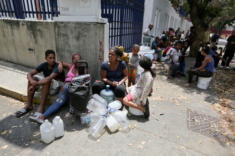 Algunas personas esperan su turno para llenar contenedores con agua de una fuente pública en Caracas, el miércoles 13 de marzo de 2019.