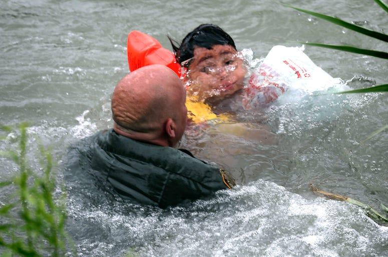 En esta foto del 10 de mayo de 2019, el agente de la Patrulla Fronteriza Brady Waikel rescata a un niño hondureño de 7 años que cayó de una balsa al cruzar el río Bravo cerca de Eagle Pass, Texas, EEUU.