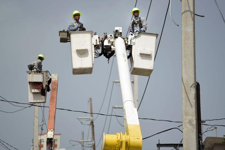 En esta foto de archivo del 19 de octubre de 2017, trabajadores de la Autoridad de Energía Eléctrica de Puerto Rico trabajan en l neas dañadas por el Huracán María en San Juan, Puerto Rico.