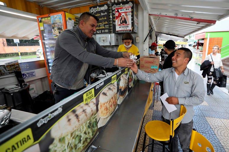 """n esta imagen del 11 de junio de 2019, Gerson Brice o, propietario del restaurante de comida r pida """"Arepas Cafe"""", sirve a un cliente en Bogotá, Colombia, el martes 11 de junio de 2019"""